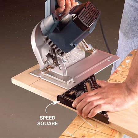 <b>Photo 2: Hold the Speed Square tight</b></br> Line up the front of the blade with the cutting mark. Slide the Speed Square against the base plate and then hold it tight against the board.