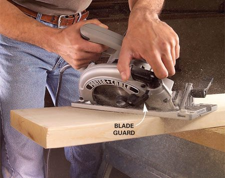 <b>Photo 2: Release the guard</b></br> Release the blade guard gently and continue the cut. Keep the saw moving straight along the line until the saw blade clears the board.