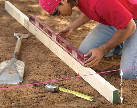 <b>Photo 4: Check the depth</b></br> Check the excavation for depth and level at a right angle to the string. Use a long straight 2x4 and a 4-ft. level.