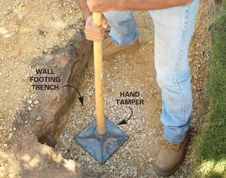 <b>Photo 5: Tamp the gravel</b></br> Spread 4 in. of compactible gravel in the wall trenches, rake it level, then compact it with a hand tamper. Moisten the gravel slightly for better packing.