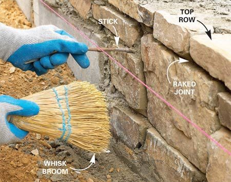 <b>Photo 11: Rake the mortar</b></br> Set the top row flat and level. When the mortar is stiff, rake it back 1 in. from the face of the stone with a stick. Brush loose mortar away with a whisk broom. If the mortar smears, stop and let it set longer before brushing.