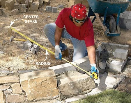 <b>Photo 13: Check the radius as you work</b></br> Check the radius for each stone with a tape measure. Taper the wall slightly inward by shifting the top edges of the stones in about 1/2 in. per foot of height. Keep the stones roughly level. Rake the joints as the mortar stiffens.