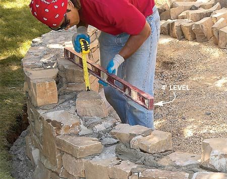 <b>Photo 15: Level the top row</b></br> Lay the top row perfectly level. Measure down from the top and find or break stones to fit the top course. As before, fill the voids inside the wall with mortar and scrap rock. Then cut the capstones to fit and set them in mortar.