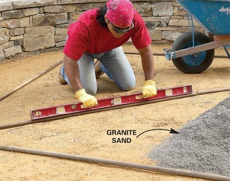 <b>Photo 17: Spread and screed granite sand</b></br> Reset the pipes and double-check your slope. Make minor adjustments by slipping sand under the pipes. Then spread granite sand between the pipes and screed it off even with the tops. Remove the pipes.