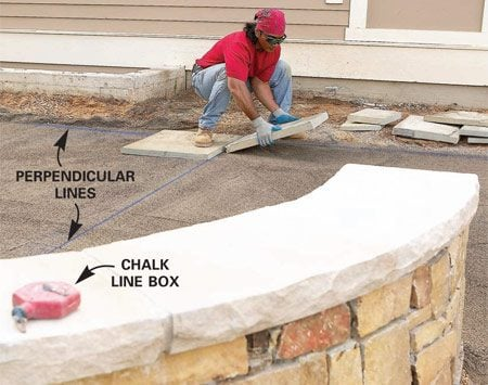 <b>Photo 18: Snap layout lines</b></br> Snap a chalk line along the side of the patio parallel to the house and another at a right angle to it down the center of the patio. Start setting stones at the intersection, staggering the joints and working outward in a pyramid shape.