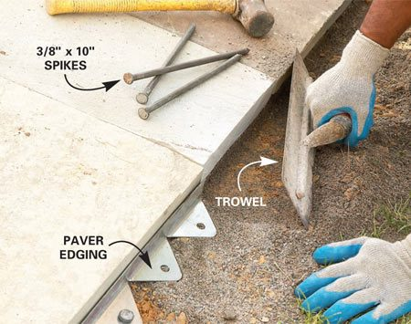 <b>Photo 23: Add paver edging at the borders </b></br> Scrape away the sand along the edge of the patio with a trowel. Support the edge with paver edging, driving a 10-in. spike to anchor it about every foot. Then sweep granite sand into the patio joints to fill them.
