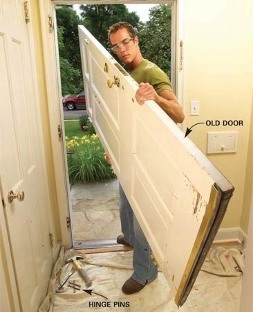<b>Photo 1: Remove the old door</b></br> Tap the hinge pins loose with a hammer and nail set. Then swing the door open and lift it off. Protect the floor with a dropcloth. The old door will be heavy.