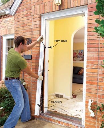 <b>Photo 3: Pry off the exterior trim</b></br> Slice the caulk joint between the siding (brick) and exterior trim and pry the trim from the doorjamb with a pry bar.