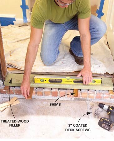 <b>Photo 5: Install the sill</b></br> Build up the sill area to the proper height with treated lumber. Add shims to level it. Fasten it with coated deck screws.