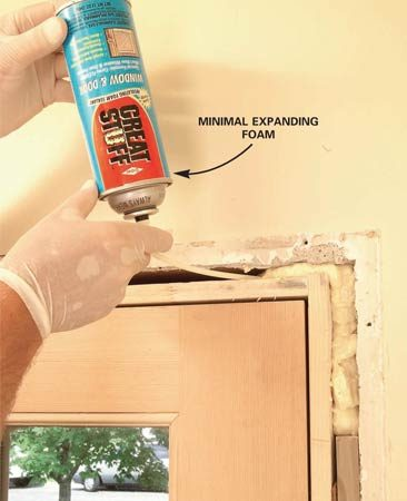 <b>Photo 12: Insulate around the door</b></br> Fill the space between the doorjamb and the framing with minimal expanding foam insulation. After the foam has expanded and skinned over, loosely stuff any remaining space with strips of fiberglass insulation.