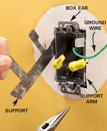 <b>Photo 4: Anchor the box</b></br> Insert the wires through the box clamps and insert the new box. Slip metal box supports along each side and bend the arms around the box edges to anchor it solidly. Mount the fixture.
