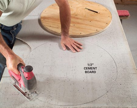 <b>Photo 10: Cut the cement board disc</b></br> Place the disc on a piece of 1/2-in. cement board and trace the circle. Then cut it out with a jigsaw fitted with an abrasive cutting blade.