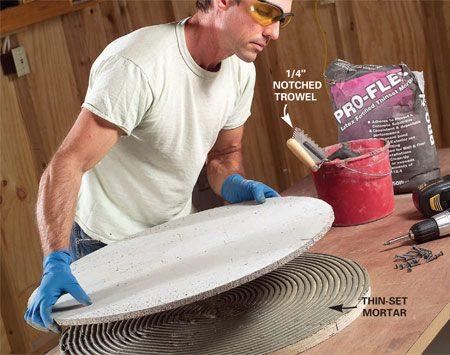 <b>Photo 11: Bond the cement board and plywood</b></br> Mix about 1-1/2 qts. of thin-set mortar to a toothpaste consistency. Let the mortar stand for 10 minutes, then spread it onto one side of your disc with a 1/4-in. notched trowel. Screw the cement board to the plywood with 1-1/4 in. cement board screws.
