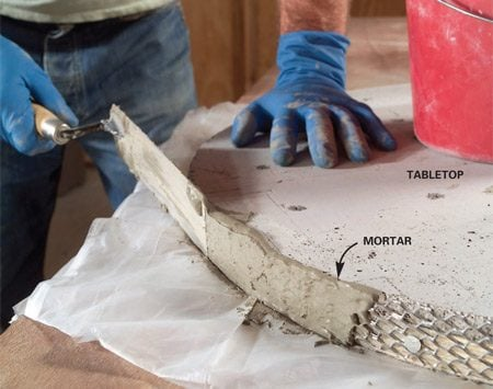<b>Photo 13: Cover the lath with mortar</b></br> Set the disc on a plastic sheet and mix about 1 qt. of thin-set mortar. Embed the mortar in the lath. Let it dry overnight. Then smooth off ridges and edges with a rasp.