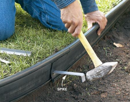 <b>Photo 4: Spike the edging to the sod</b></br> Hold the top of the tube about an inch above the sod and drive spikes every 5 ft. through the edging into the side of the excavation.