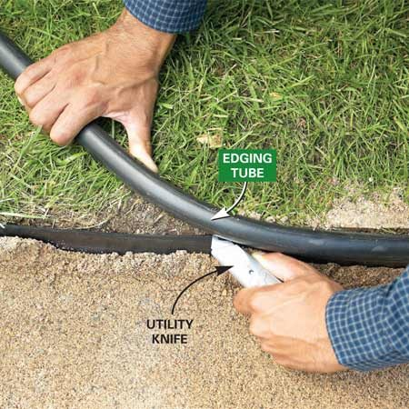 <b>Photo 8: Trim the tube</b></br> Cut the tube off the top of the plastic edging with a sharp utility knife. Keep the cut at or slightly below the soil level to keep it out of sight.