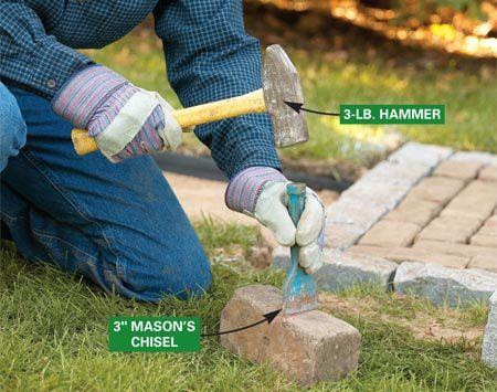 <b>Photo 12: Cut the paver</b></br> Lay the paver on the grass, set the chisel on the mark and rap it with several times with a 3-lb. hammer. Do the same on all sides until it breaks.