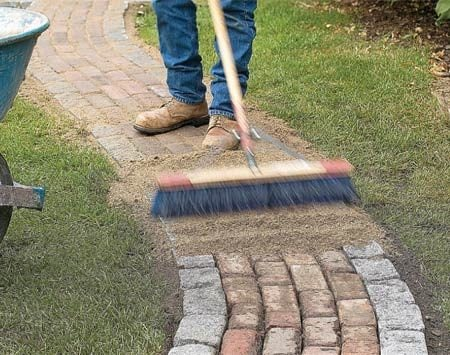<b>Photo 15: Work sand into the gaps</b></br> Sweep sand over the path, working it in until all the joints are full. Save some sand to sweep into the joints after the first rain.
