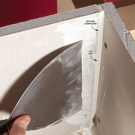 <b>Photo 1: Fill wide gaps with setting-type compound</b></br> Mix the setting compound and completely fill all wide gaps. Don't overfill. Keep the fill flush with the drywall surface.