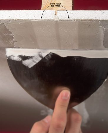 <b>Photo 1: Taping a butt joint</b></br> Since butt joints don't have tapered edges, apply thin layers of compound below and on top of the tape to avoid a large bump in the wall.