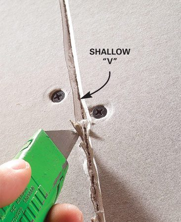 <b>Photo 2: First, cut away loose paper</b></br> Trim away loose drywall paper to prevent lumps and bubbling under the tape.