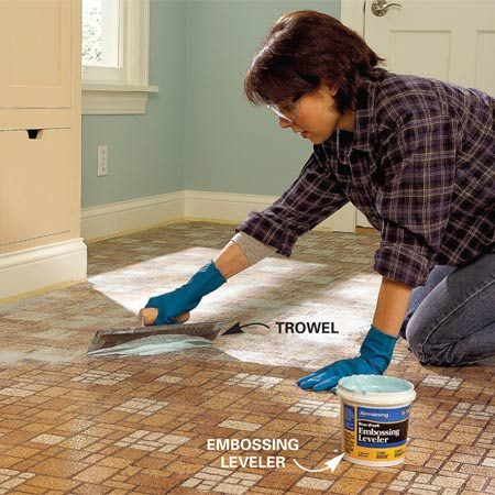 <b>Photo 2: Spread a filler to even the surface</b></br> Fill embossed patterns and minor imperfections with embossing leveler. Spread a thin, even layer over the floor with the flat side of a trowel. Hold the trowel at a 60-degree angle to the floor and trowel diagonally across the pattern. Let the leveler dry for the recommended time.