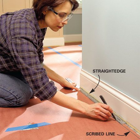 <b>Photo 5: Use a spacer to scribe</b></br> Scribe the shape of the floor onto the paper template by holding a straightedge against the baseboard while you draw a line along the inside edge.