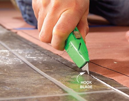 <b>Photo 9: Cut just outside the line </b></br> Cut out the vinyl flooring using a utility knife fitted with a new hook blade. Cut about 1/8 in. inside the line where the edge will be covered with base shoe. Cut along the line itself where the edge will be left uncovered.