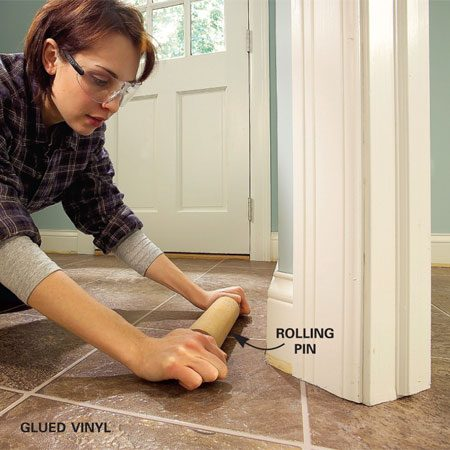 <b>Photo 13: Secure the flooring to the adhesive</b></br> Roll the flooring from the center out with firm pressure on a rolling pin. Press the edges with a wallpaper roller.