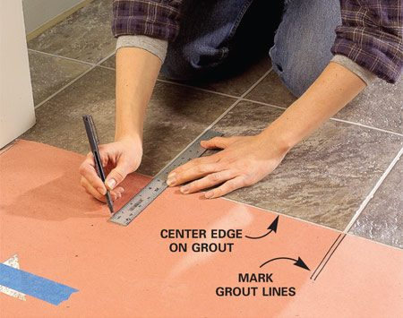 <b>Photo 1: Align the pattern</b></br> Align the edge of the template paper with the exact position of the desired seam and mark the pattern (grout line) locations. Line up the edge of the template with a grout line on the new vinyl and align the grout line marks. Tape the template to the new vinyl. Leave a few extra inches of vinyl at the seam location. Follow the steps in Photos 8 – 13 for cutting and positioning the new piece, being careful to position the seam location precisely. Then glue down the vinyl.