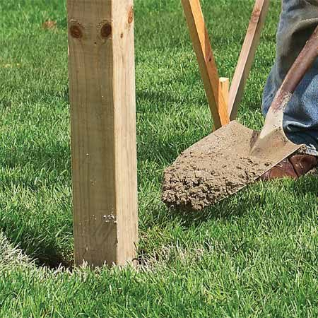 <b>Photo 4: Anchor posts with concrete</b></br> Mix concrete and fill each hole. Mound the concrete about 1/2 in. above the ground level and slope it away from the post. Let it set overnight.