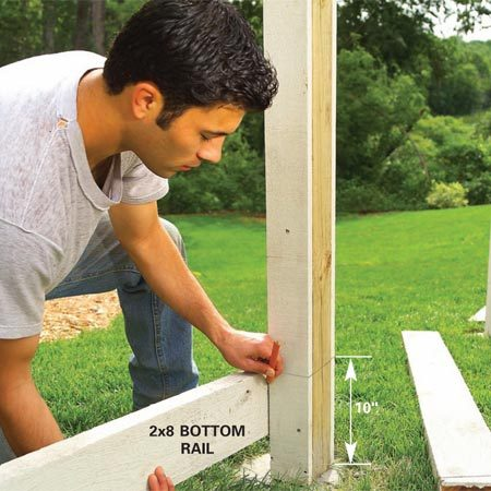 <b>Photo 6: Mark the lower rail height</b><br/>Hold the 2x8 against the posts 10 in. above the concrete and scribe both ends. Cut the rails to length, minus 1/8 in. for clearance.