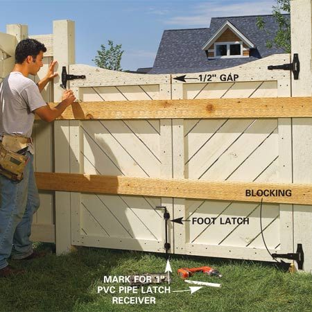 <b>Photo 19: Space and hinge the gates</b></br> Space the gates 1/2 in. apart on the ground and screw two 8-ft. boards to each. Prop the gates in the opening, space them and screw the boards to the posts. Attach the hinges and foot stop. Set the foot stop pipe and attach a 1x4 gate stop to the fixed gate, leaving a 1-in. overhang. Attach the latch.