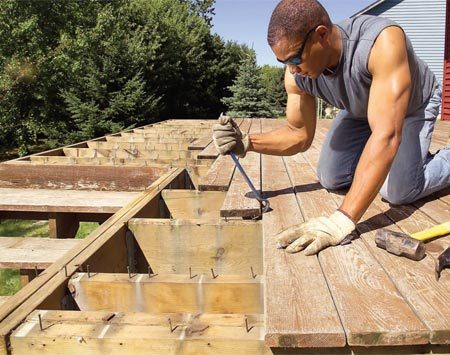 <b>Photo 1: Remove the old decking and railing</b></br> Remove the rails and begin prying up the nailed decking boards. Start from the outside and move toward the house so you have a solid, safe platform to work from.