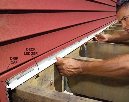 <b>Photo 3: Add drip cap</b></br> Tuck 1-1/2 in. wide drip cap under the siding and building paper and over the deck ledger to direct water away from the house.