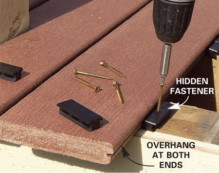 <b>Photo 7: Attach the hidden fasteners</b></br> Slip the hidden fasteners into the decking groove and screw them to the center of each joist.