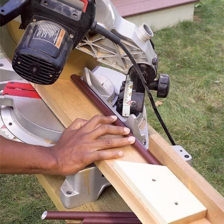 <b>Photo 20: Cut the spindles</b></br> Cut the stair spindles to length. Cut the stair angle on one end of the stair spindles, then use an angled stop block to position the spindle for a parallel cut on the other end.