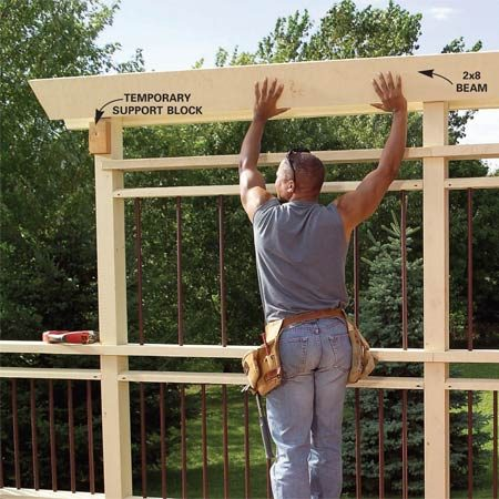 <b>Photo 25: Install the trellis</b></br> Install the second row of rails and spindles, and then cut the privacy trellis posts to length. Rest the 2x8 beams on temporary blocks and screw them to each post with three 3-in. deck screws.