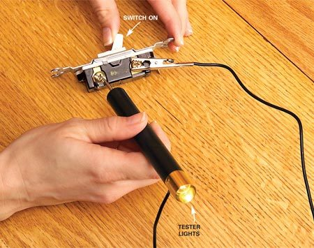 <b>Photo 2: Test switches</b></br> Test a switch. Remove the switch, then clip one lead to one switch terminal. Touch the point to the other terminal and flip the switch on and off. The tester light will go on and off if the switch is good.