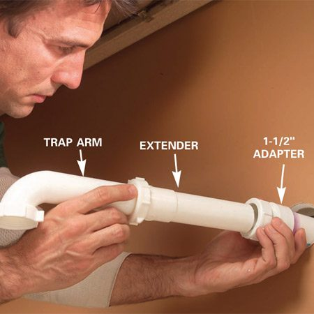 <b>Photo 2: Place the trap arm under the tailpiece</b></br> Slide the trap arm into the adapter. Then attach the trap and slide the arm in or out to position the trap directly under the tailpiece. You may need to cut the arm or add an extender.