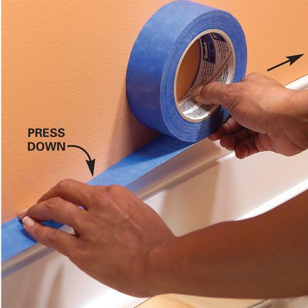 <b>Photo 2: Press it down</b></br> Lay the tape roll flat against the wall and rotate the roll to tighten and straighten it. Slide your finger across the tape to press it down.