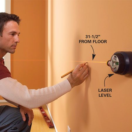 <b>Photo 2: Establish a level line</b></br> Measure up the wall 31-1/2 in. and use a level or laser level to mark a level line around the entire room. Mark stud locations using a stud finder.