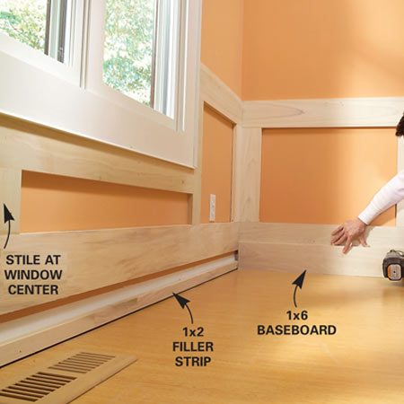 <b>Photo 14: Nail the baseboard</b></br> Nail the 1x2 filler strips to the wall near the floor. Then nail the 1x6 baseboard to the filler and the lower rail.