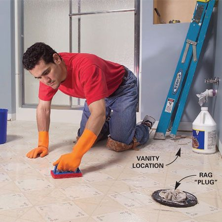 <b>Photo 1: Scrub the floor with stripper</b></br> Remove the baseboard and toilet. Using an abrasive pad, scrub the floor hard with water mixed with vinyl floor stripper.