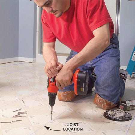 <b>Photo 2: Drive screws into the floor joists</b></br> Mark the floor joists with chalk lines and drive 2-1/2-in. screws every 8 in. Don't leave any screw heads protruding.