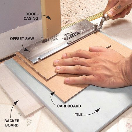 <b>Photo 3: Cut the door trim to accommodate tile</b></br> Undercut door trim using a jamb saw or handsaw. A piece of backer board, tile and two layers of cardboard raise the saw to the correct height above the floor.