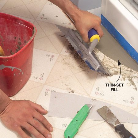 <b>Photo 4: Fill low spots with thin-set</b></br> Cut out any loose sections of vinyl with a utility knife. Fill the void with thin-set using the flat edge of a notched trowel.