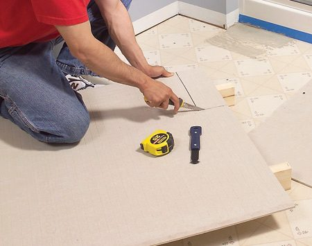 <b>Photo 5: Install backer board over the floor</b></br> Cover the floor with backer board. Cut inside corners, circles and curves with a drywall saw. Space pieces 1/8 in. apart and hold each one in place with two temporary screws.