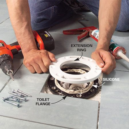 <b>Photo 13: Install an extension ring over the toilet flange</b></br> Remove the old screws from the toilet flange and apply a heavy bead of silicone caulk. Fasten the extension ring over the old flange with stainless steel or brass screws.