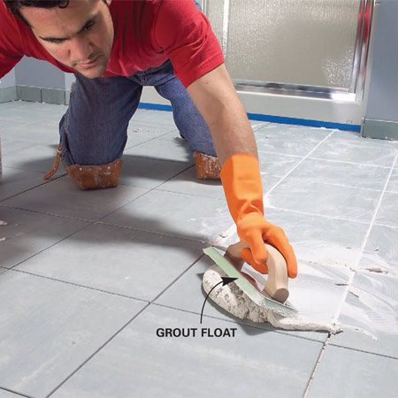 <b>Photo 16: Grout the joints</b></br> Work the grout back and forth across the floor, diagonal to the joints and holding the float at a 45-degree angle. Then scrape off the excess grout, holding the float almost upright.
